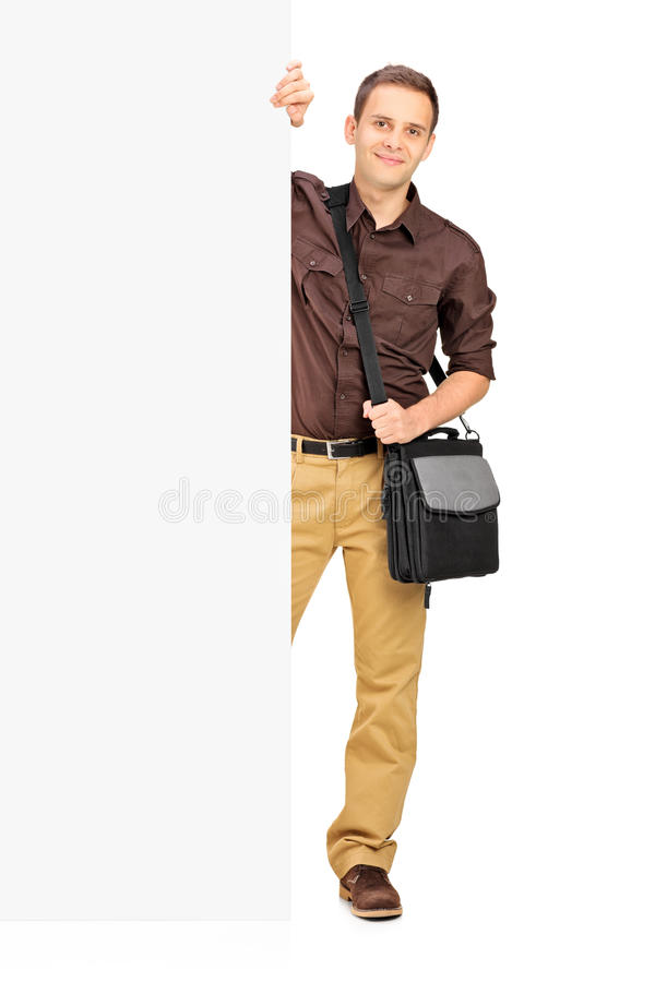 Young male student standing behind a panel royalty free stock photos