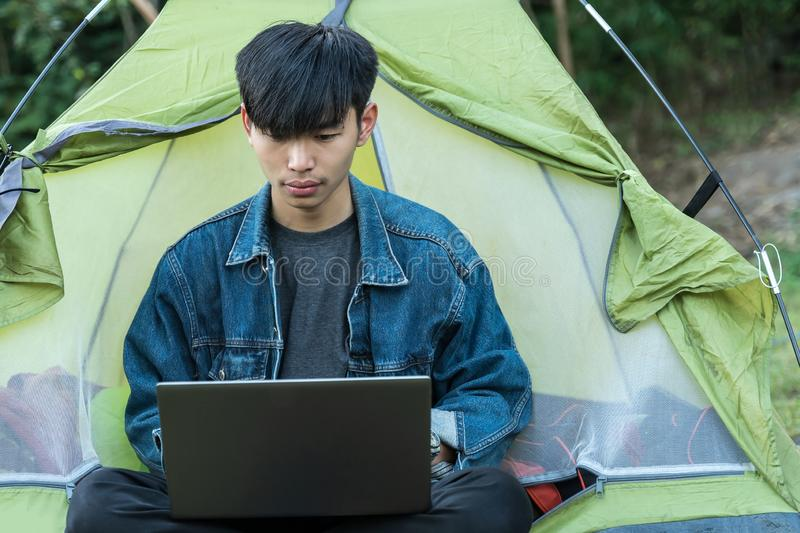 Young male student using laptop while goes camping in forest in relaxing vacation. royalty free stock image