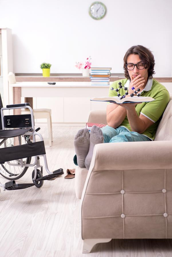 Young male student in wheelchair at home stock photography