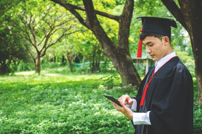 Young male students dressed in black graduation gown. Nature as a background. Boy cheerfully smiling, looking at mobile phone royalty free stock images