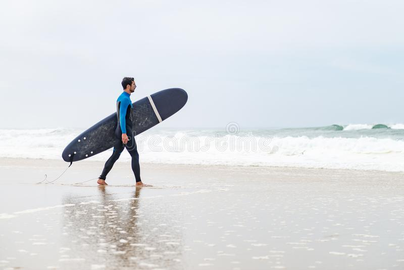 Young male surfer wearing wetsuit stock photos