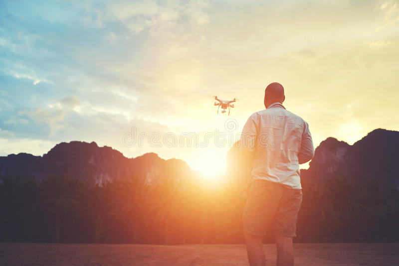 Young male is taking photo on modern flying remote camera during summer trip. Silhouette of a man photographer is shooting video with multirotor RC quadcopter stock image