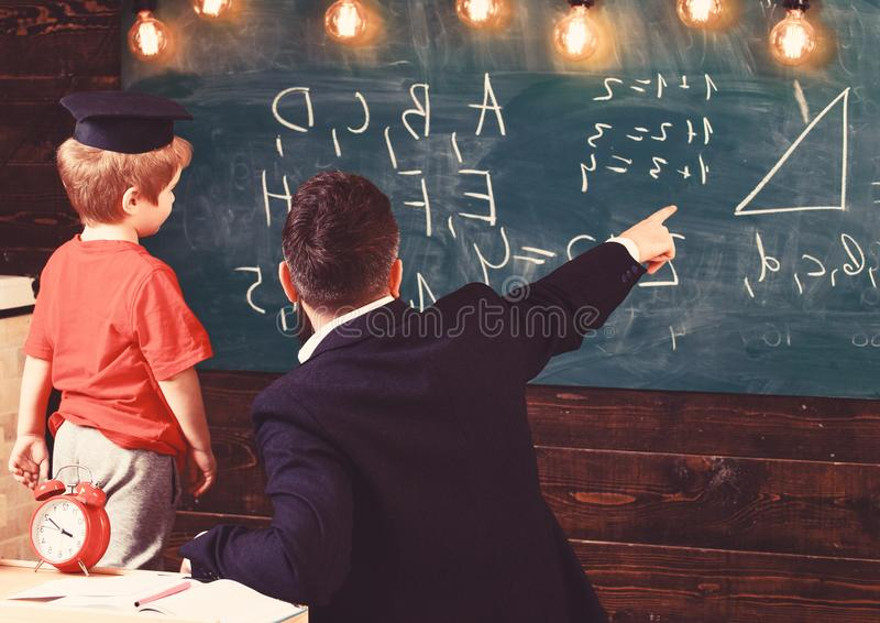 Young male teacher guides his child student to learning while pointing and looking at chalkboard with scribbles on royalty free stock images