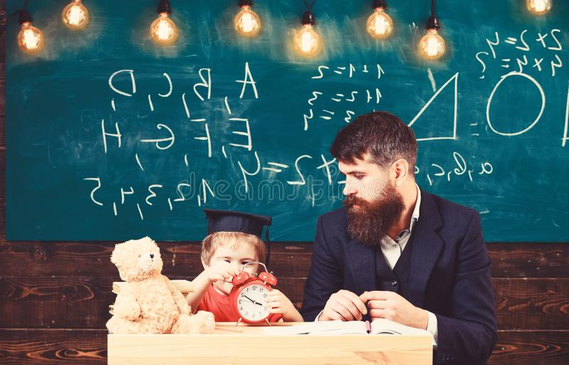 Young male teacher guides his child student to learning while sitting in classroom with scribbles on chalkboar royalty free stock photos
