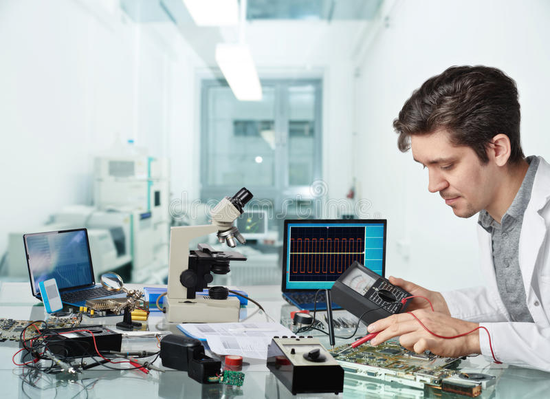Young male tech or engineer repairs electronic equipment stock photo