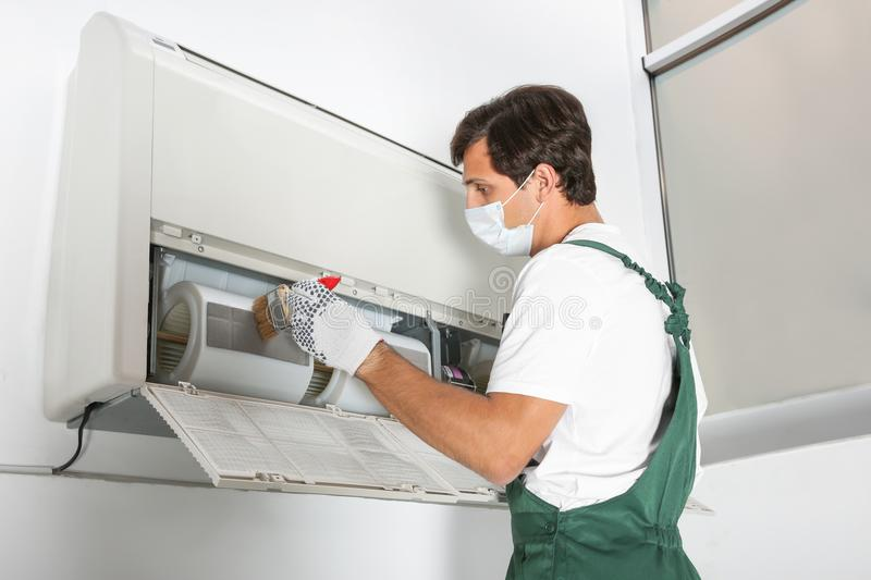 Young male technician cleaning air conditioner royalty free stock photography