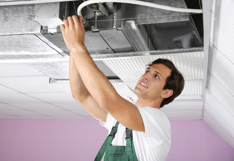 Young male technician repairing air conditioner stock photo