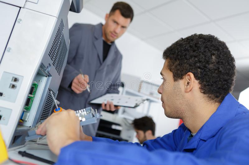 Young male technician with teacher repairing digital photocopier machine royalty free stock photography