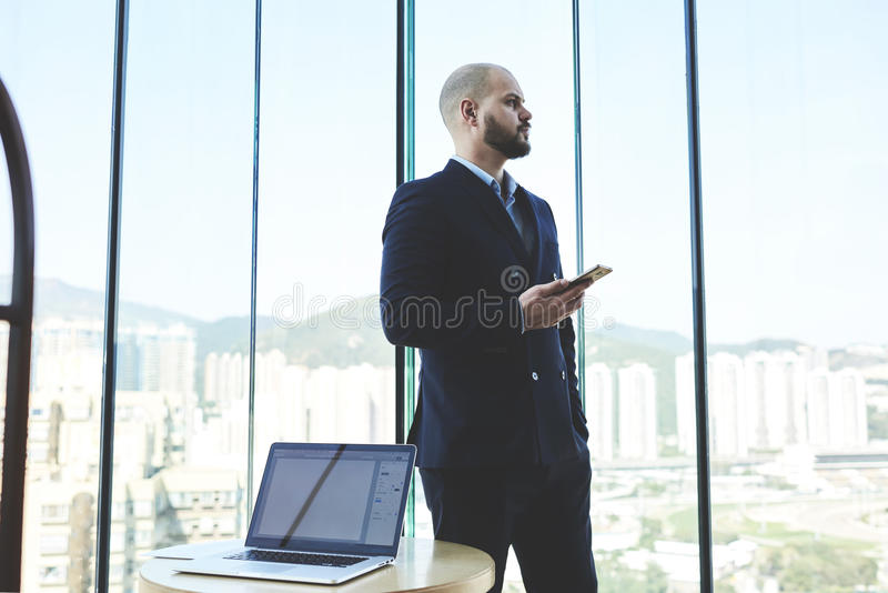 Young male is thinking about something serious. Confident man broker in suit is holding mobile phone, while is standing in office of brokerage company near table stock photography