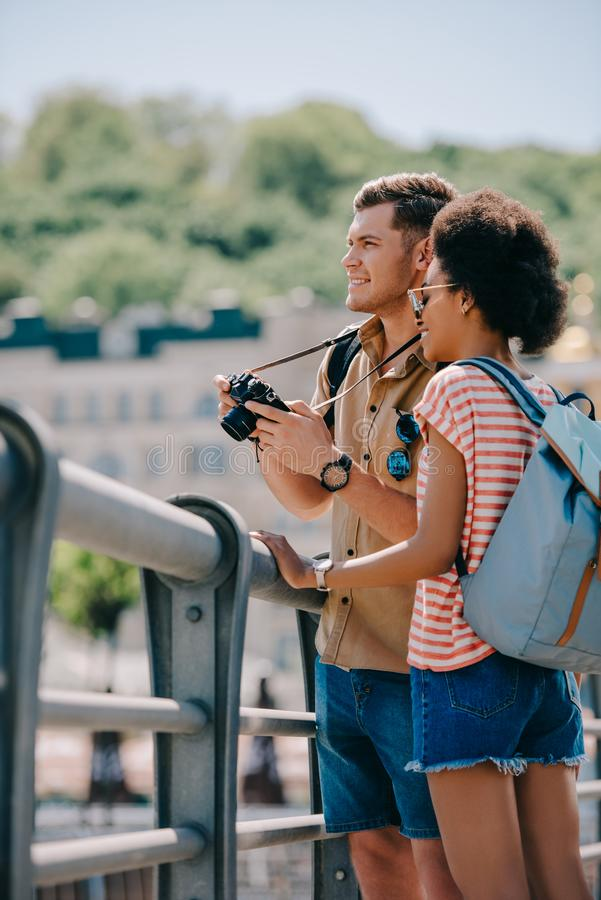 Young male tourist with camera and african american girlfriend royalty free stock images