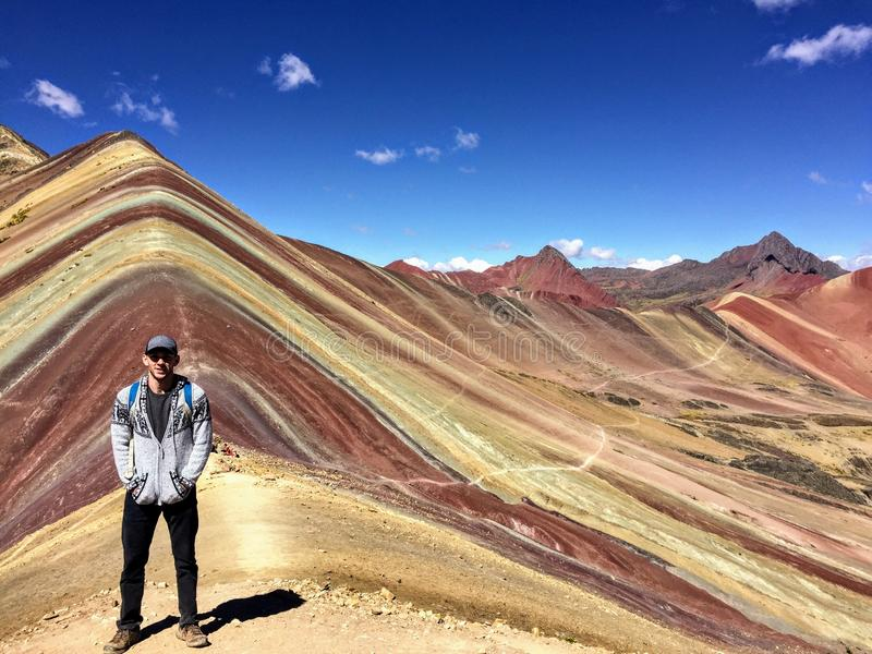 A young male tourist enjoying the view of the incredible Rainbow Mountains outside of Cusco, Peru. The amounts are a variety of colours from the mineral royalty free stock photo