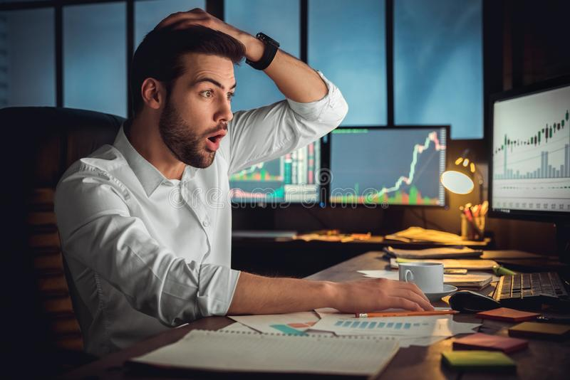Young male trader at office work concept sitting looking at screen shocked stock photography