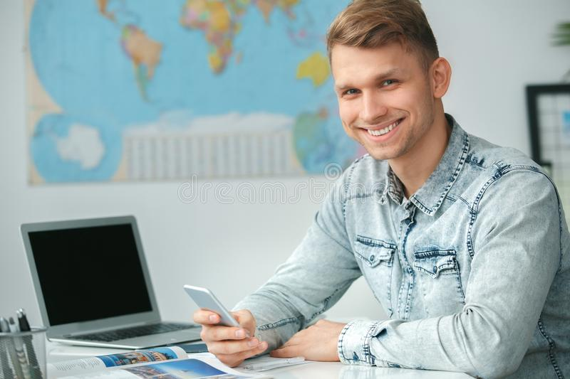 Young male travel agent consultant in tour agency holding smartphone. Young man travel agent in tour agency sitting using smartphone looking camera smiling stock image