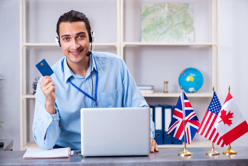 Young male travel agent working in the office royalty free stock photos