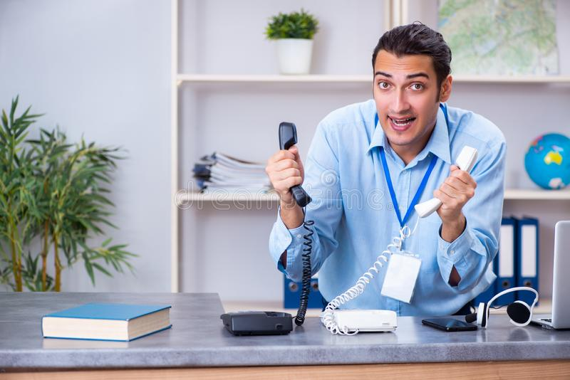 Young male travel agent working in the office stock photo