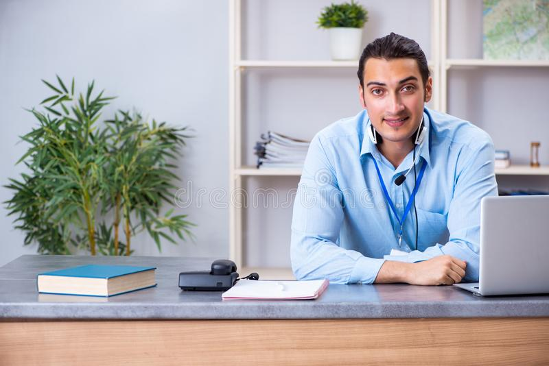 Young male travel agent working in the office stock image