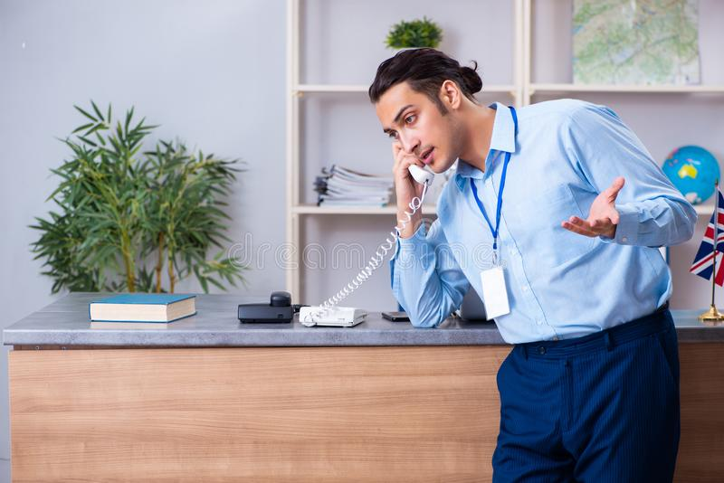 Young male travel agent working in the office royalty free stock image