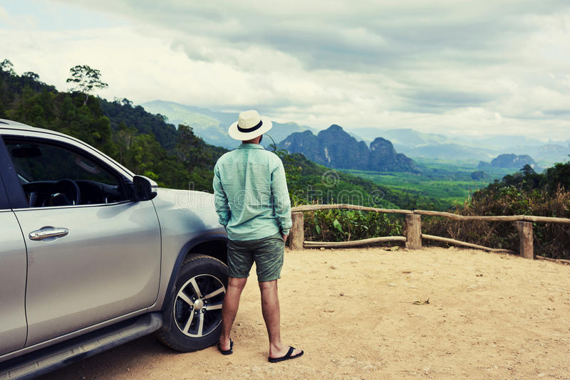 Young male traveler is enjoying beautiful landscape during road trip on suv in Thailand. Back view of a man is thinking about this amazing world, while is stock image