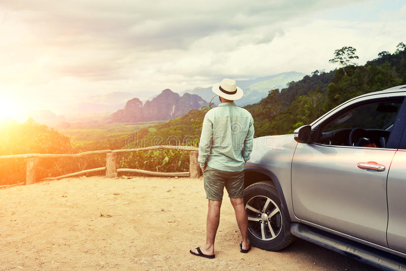Young male traveler is enjoying beautiful landscape during road trip on suv in Thailand. Back view of a man is thinking about this amazing world, while is stock photo