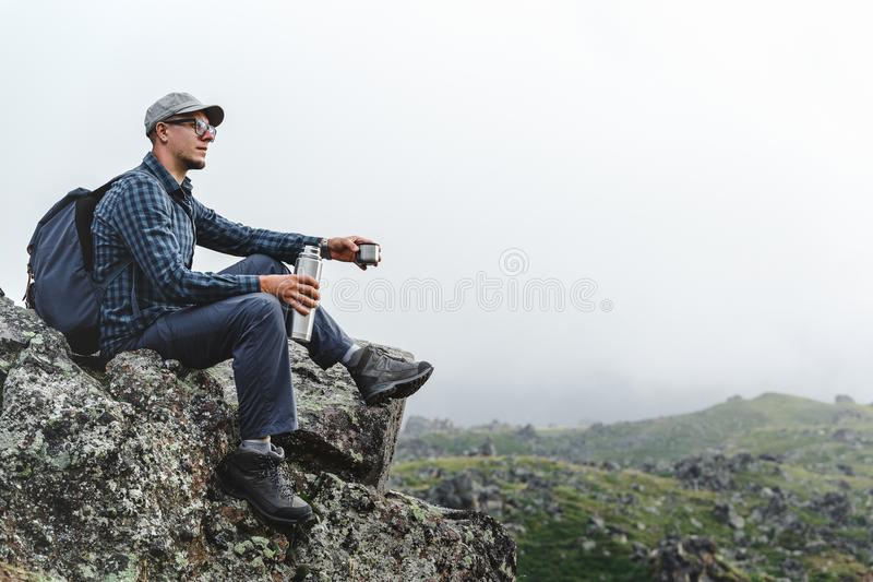 Young Traveler Man Sitting On Top And Holding Thermos In His Hand. Hiking Adventure Tourism Concept. Young male traveler in a shirt, sitting on a rock and royalty free stock images