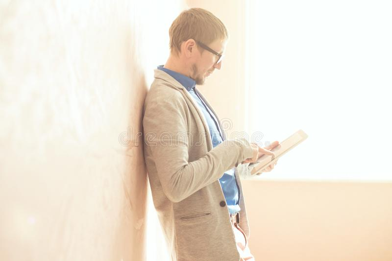 Young male using digital tablet against wall in sunny day royalty free stock photography