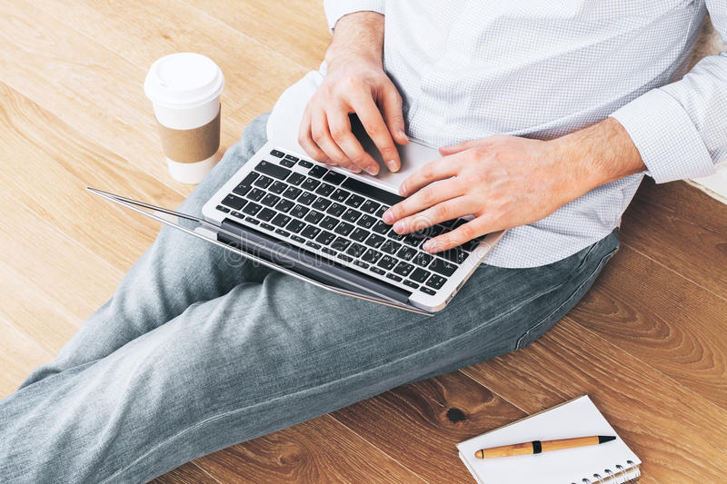 Young male using laptop floor stock image