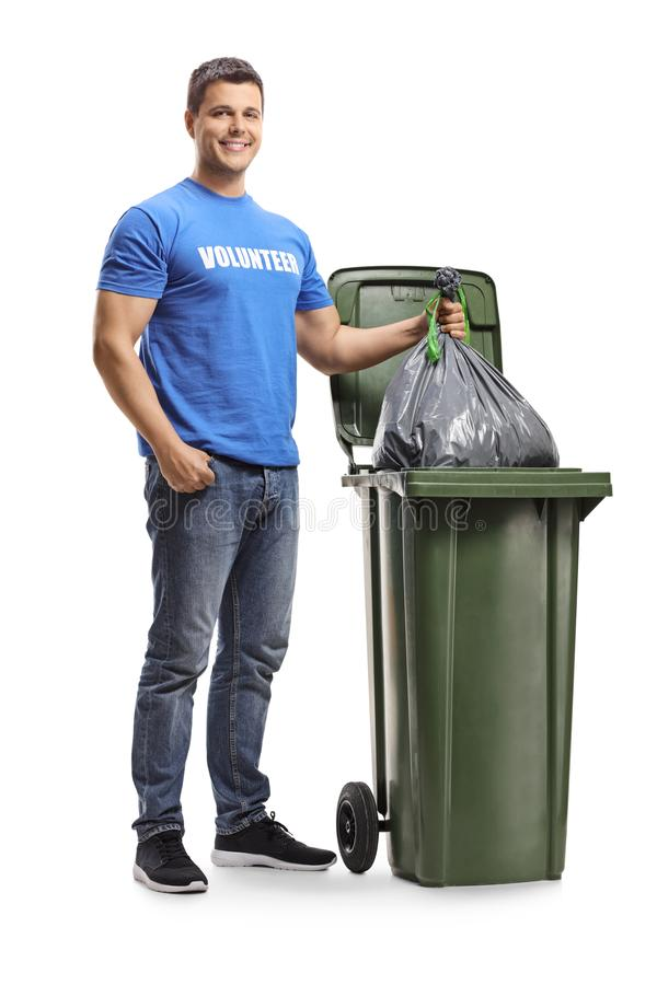 Young male volunteer throwing a plastic bag in a bin. Full length portrait of a young male volunteer throwing a plastic bag in a bin isolated on white background stock image