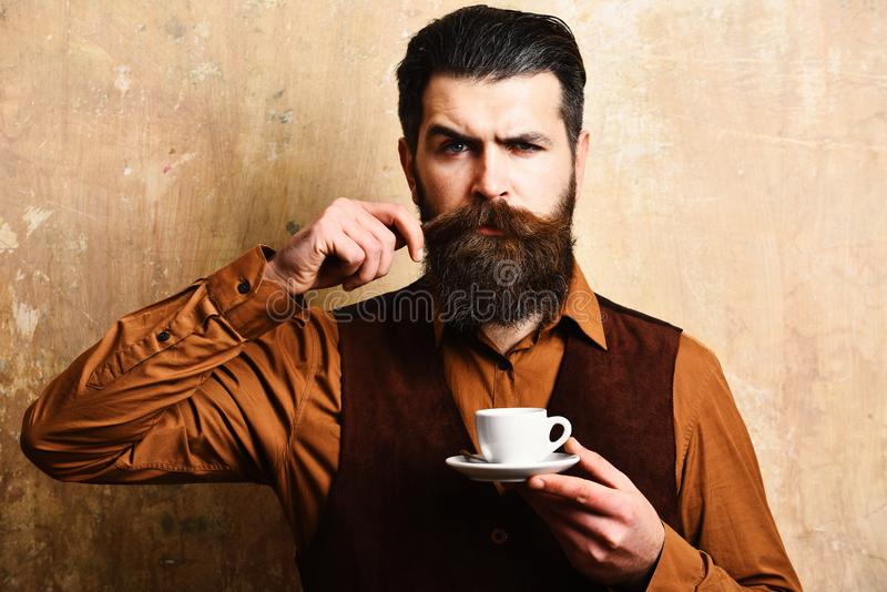 Young male waiter in uniform holding cup of coffee stock image