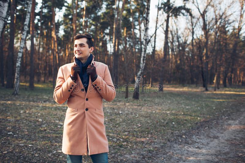 Young male walking in the forest in nature in a cream coat. Young male gulet in the woods in nature in a cream coat royalty free stock images