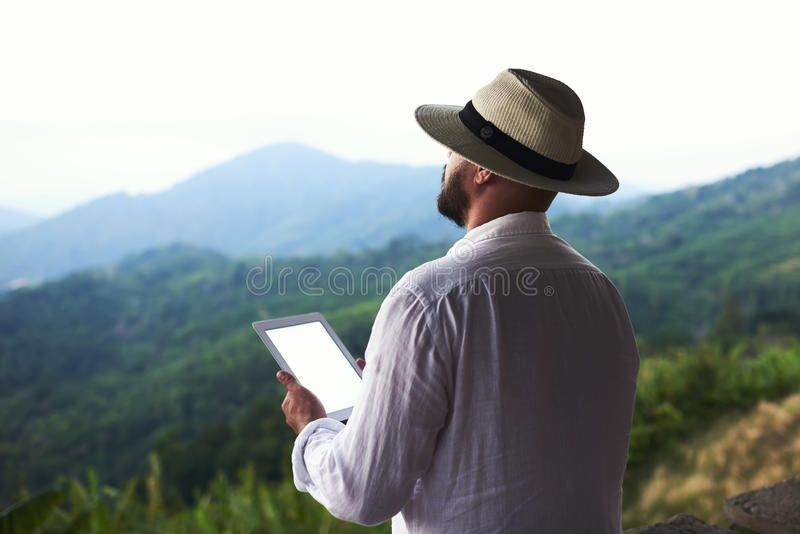 Young male wanderer with digital tablet in hands is enjoying wonderful Amazon scenery. Man traveler is sun hat is holding portable touch pad with copy space on royalty free stock photography