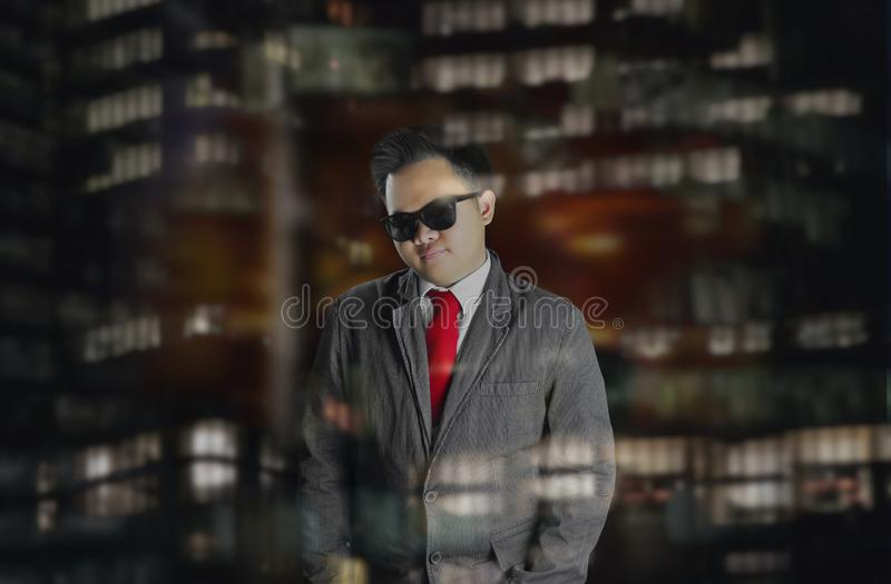 Young male wearing suit and red tie with sunglasses. Night scene at the city. royalty free stock photography