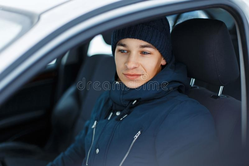 Young male in winter clothing sitting in a car stock photos