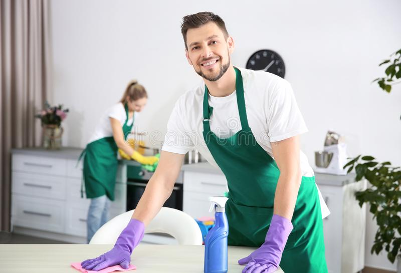 Young male worker of cleaning service working in kitchen royalty free stock photography