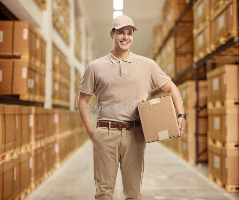 Delivery man holding a package in a storage royalty free stock image