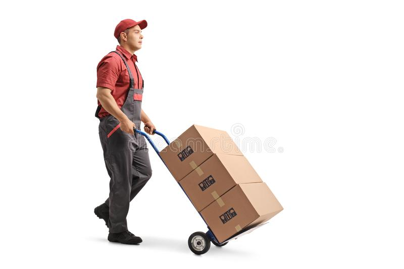 Young male worker in a uniform pushing boxes on a hand truck royalty free stock photos