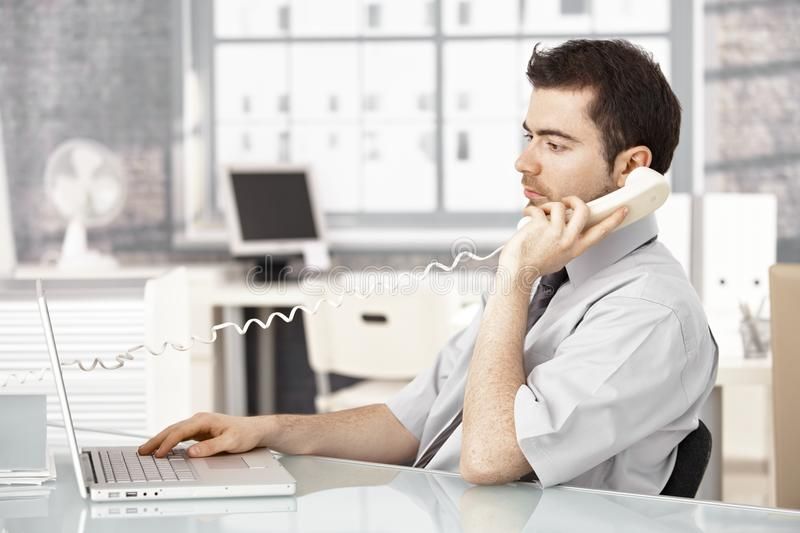 Young male working in office talking on phone stock photos