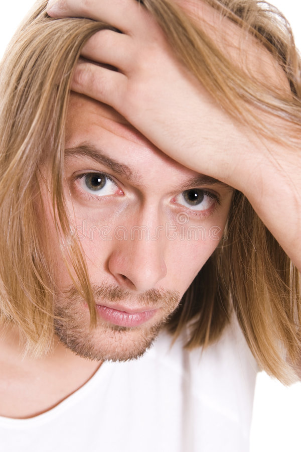 Young man. Having headache, long hair stock photography