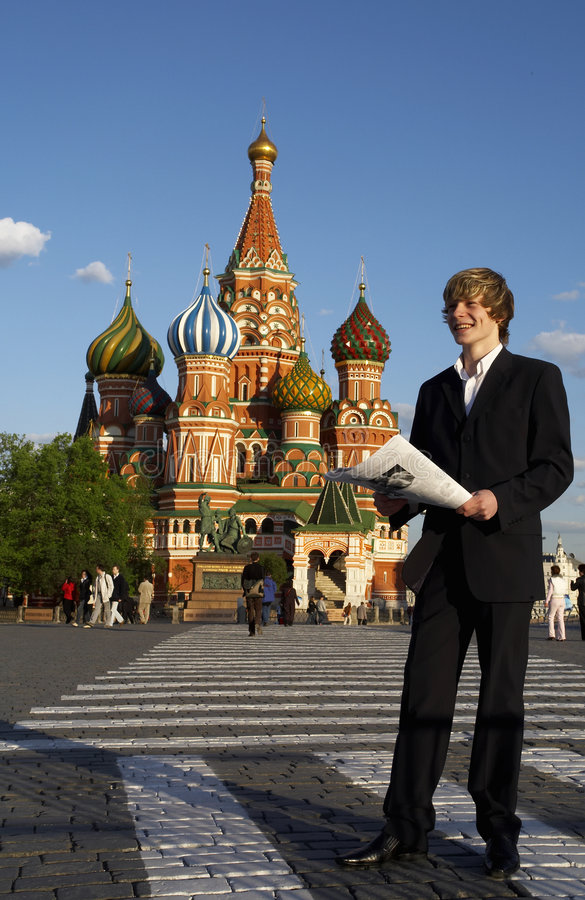 Young the man. Young the business man reads the newspaper in Russia on the red area stock photography