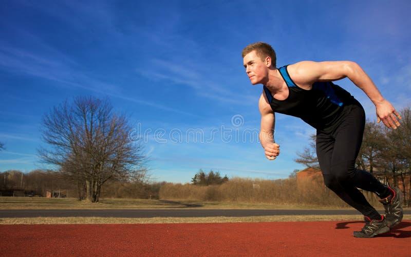 Young man accelerating into sprint. A young man on a sportstrack accelerating into sprint royalty free stock photos