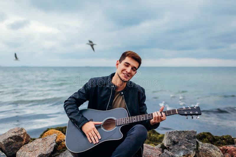 Young man with acoustic guitar playing and singing on beach surrounded with rocks on rainy day stock image