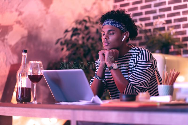 Young man adjusting earbuds to better work with portable computer while drinking wine. Hardware setup. Young concentrated man adjusting new earbuds to better stock images