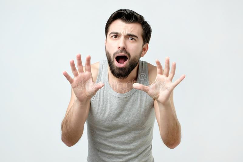 Young man is afraid and terrified with fear expression stop gesture with hands royalty free stock photography
