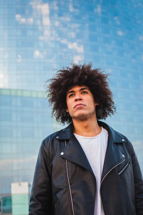 Young man with afro hair with modern urban background stock photo