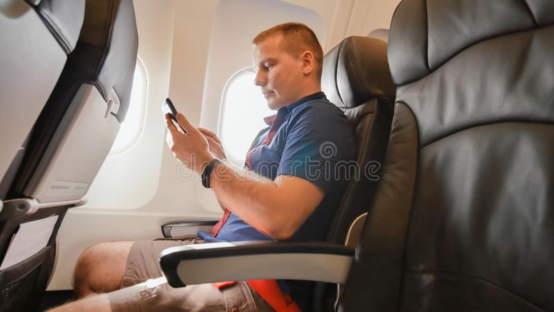 A young man in an airplane before a flight communicates on a mobile phone. stock photos