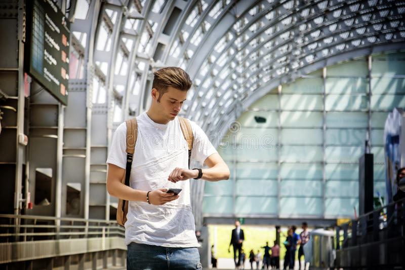 Young man at airport or station, looking at wrist watch. Handsome young man waiting in airport or station, looking at his wrist watch royalty free stock photography