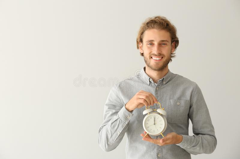 Young man with alarm clock on light background stock photography