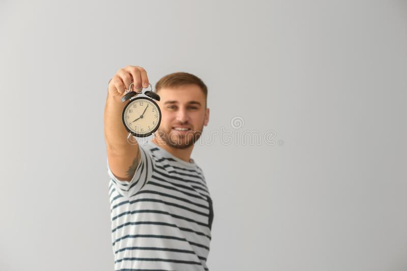 Young man with alarm clock on white background royalty free stock photos