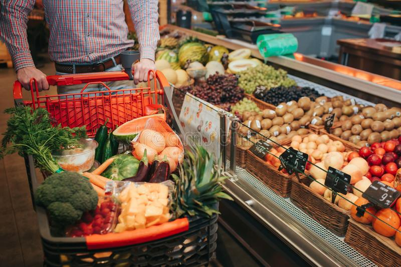 Young man alone in grocery store. Cut view guy hold trolley hand. Basket full of vegetables and fruit. Standing at royalty free stock images