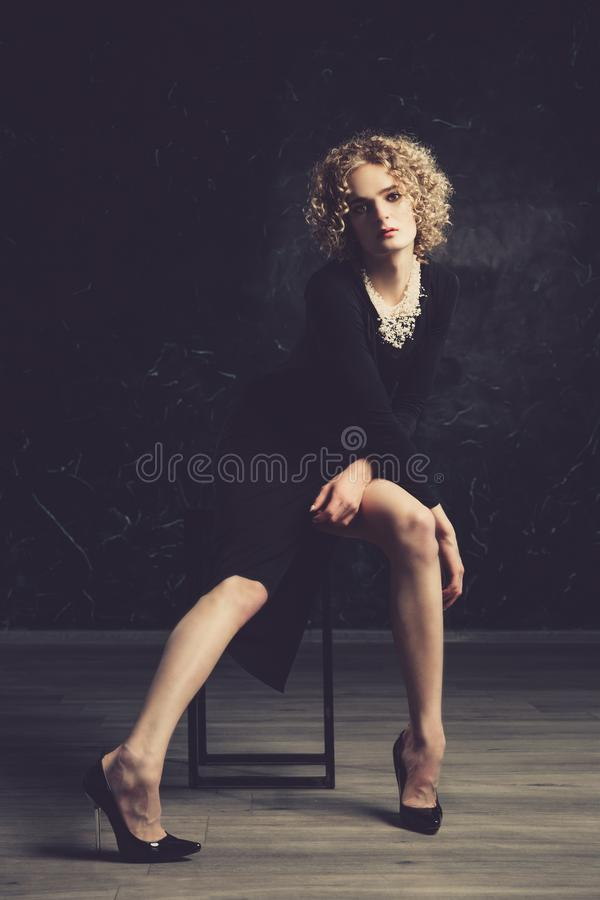 Young man androgyne model in the image with an afro hair and makeup posing sitting on the chair. stock images