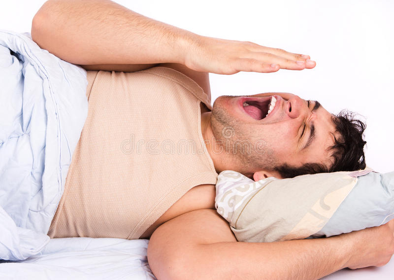 Young man annoyed by the noise. Young man in bed , trying to sleep stock photo